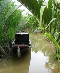 Boat in a stream on Cồn Tàu (Ship Island) in the Mekong Delta.