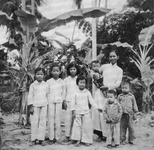 Lunar New Year (Tết) 1964 in front of the house in Quới Sơn. Má holds Lượng (6 months). Siblings from left to right: Huệ (Chị Tư), Lan (Chị Ba), Thanh (Chị Hai), Thơm (Chị Năm), Thượng (Anh Bảy), and Vân (Anh Sáu).
