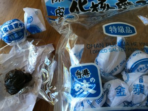 A package of wrapped dried salted pitted plums and an unwrapped one (similar to Chinese medicine balls).