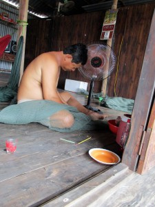 A fisherman repairing a net while sitting on the floor of his house in rural Vietnam.